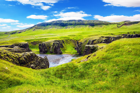 striking: The concept of active northern tourism. The striking canyon in Iceland. Bizarre shape of cliffs surround the stream with glacial water. Green Tundra in July