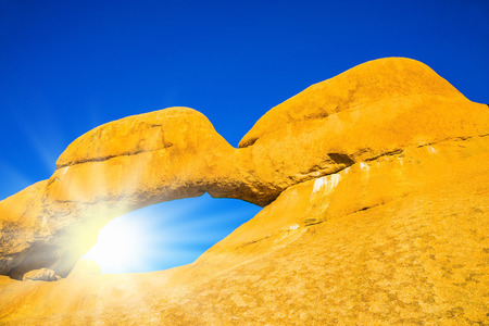 turismo ecologico: The concept of extreme and ecological tourism. Natural array of bald granite outcrops and stone arch Spitzkoppe, Namibia. The hot African sun over the Namib Desert