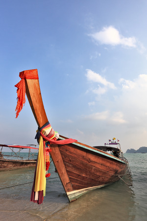 Orange Thai boat for tourists. Bow is decorated with colorful and bright silk scarves