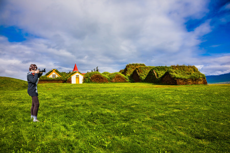 The elderly woman photographed the old village. Ethnographic Museum-estate Glaumbaer, Iceland. The concept of the historical and cultural tourism Editorial