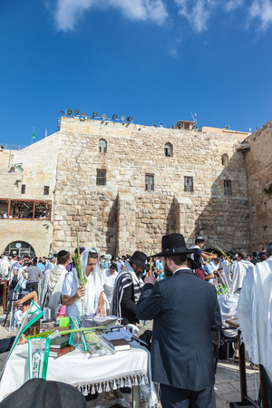 JERUSALEM, ISRAEL - OCTOBER 12, 2014: The area in front of the Western Wall of the Temple filled with people. Morning autumn Sukkot. Many brought prayer books and four ritual plants