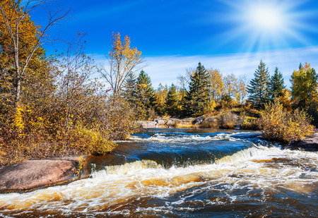 rifts: Foamy water rifts on smooth stones and low fir-trees on river banks Winnipeg. The concept of ecological and extreme tourism. Autumn northern sun in Old Pinava Dam Stock Photo