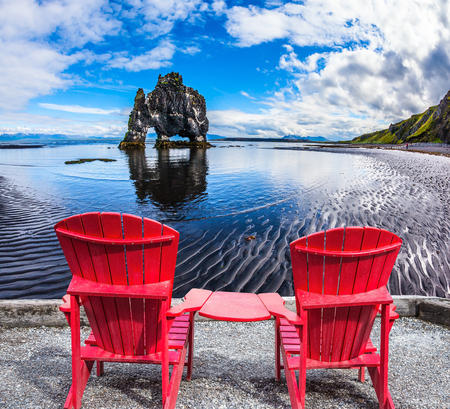 outflow: Pair of comfortable red deck chairs set in front of Magic Rock Hvitsercur. Northern coast of Iceland. Concept of extreme northern tourism