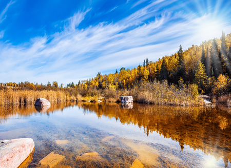 The concept of travel Around the World.  Yellow autumn grass and pale northern sun is reflected in the Winnipeg River. Old Pinawa Dam Provincial Heritage Park Stock Photo