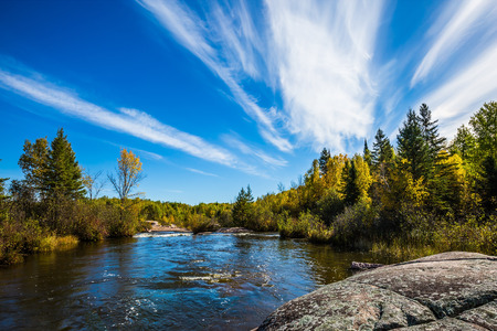 Tranquil landscape in the Old Pinawa Dam Park. Thin cirrus clouds and foam on the Winnipeg River. Trend of travel Around the World