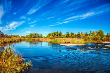 Thin cirrus clouds and broad Winnipeg River. Tranquil landscape in the Old Pinawa Dam Park. Trend of travel Around the World