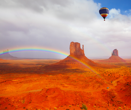Huge balloon flies over Red Desert Navajo, USA. The picturesque rainbow crosses some rocks - mitts