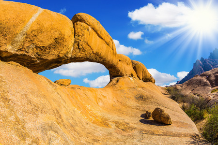 Natural array of bald granite outcrops im Namibia. The hot African sun over stone arch Spitzkoppe, the Namib Desert. The concept of extreme and ecological tourism