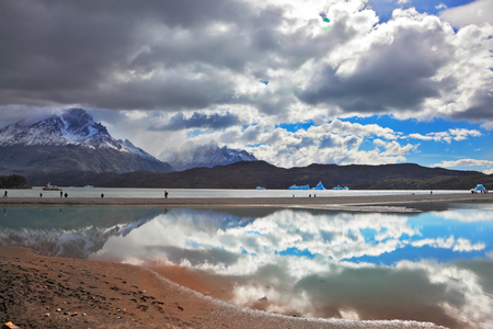 The mysterious glow. Bright reflections of sky and clouds in the smooth cold water of Lake Grey. Chilean Patagonia, National Park Torres del Paine