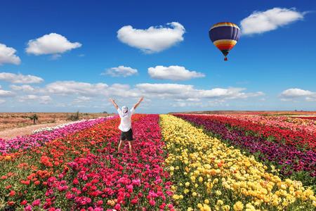 vómito: turistas entusiastas levantó las manos. Gran globo vuela sobre el campo de la floración.