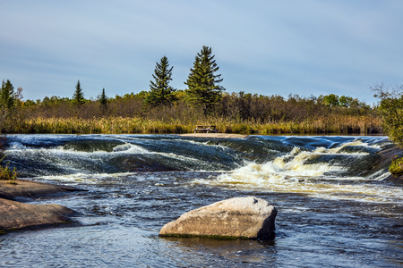 Foam water rapids on the smooth stones of the Winnipeg River. Old Pinawa Dam Provincial Heritage Park. The concept of travel Around the World. Warm autumn day
