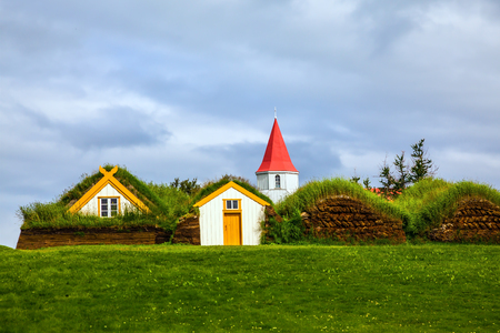 The village of old houses covered with turf and grass. Church bell tower with red gabled roof. Ethnographic Museum-estate Glaumbaer, Iceland. The concept of the historical and cultural tourism