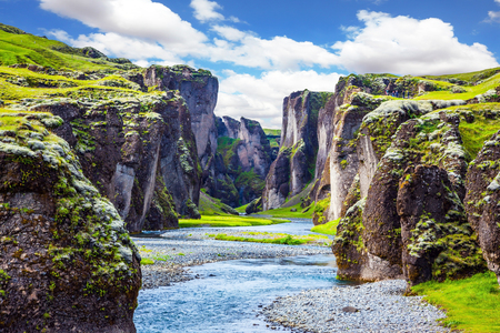 Steep cliffs, overgrown with green moss, surrounded by a very fast river with cold water. Canyon Icelandic fairy tales - Fyadrarglyufur
