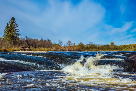 Foam water rapids on the smooth stones of the Winnipeg River. Old Pinawa Dam Provincial Heritage Park. The concept of travel Around the World
