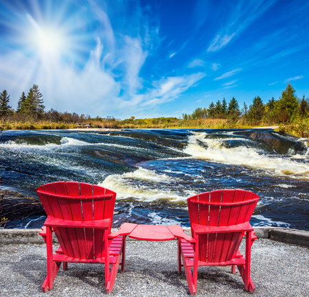 Lovely place to relax. Two red beach chairs on the riverbank. Foam water rapids on the smooth stones, cirrus clouds and strong wind. Old Pinawa Dam Park. The concept of ecological and recreational tourism Stock Photo