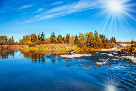 Yellow autumn grass and pale northern sun is reflected in the Winnipeg River. Old Pinawa Dam Provincial Heritage Park.  The concept of ecological tourism