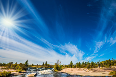 Improbable plumose clouds and the autumn sun over the river Winnipeg. Indian summer in Manitoba, Canada. The concept of ecological and recreational tourism Stock Photo