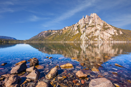 Picturesque mountain in San Carlos de Bariloche, Argentina. The mirror water of lake reflects sharp rocks. The concept of exotic and extreme tourism Stock Photo