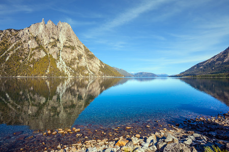 The concept of exotic and extreme tourism. The mirror water of the lake reflects sharp peaks and rocks. Pyramidal mountain in San Carlos de Bariloche Stock Photo