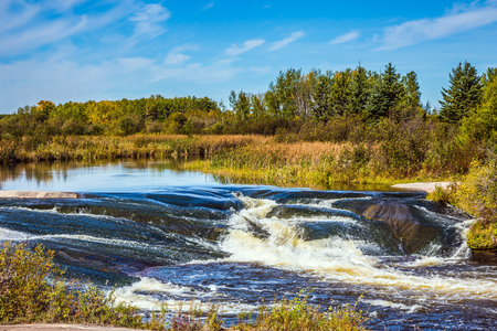 fissure: Foam water rapids on the smooth stones of the Winnipeg River. Warm autumn day. The concept of travel Around the World. Old Pinawa Dam Park Banque d'images