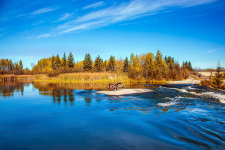 Landscape in the Old Pinawa Dam Park, Winnipeg River. Trend of travel Around the World. On the small island is a wooden bench for tourists