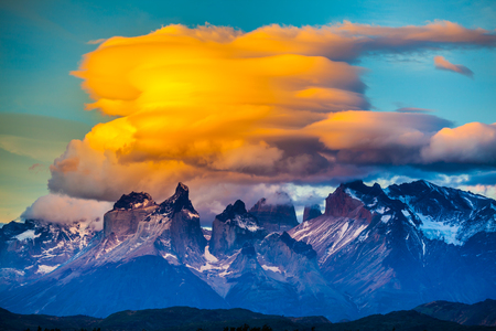Magnificent orange clouds in the rays of the sunset.  The black cliffs of Los Cuernos. The concept of extreme and active tourism. Torres del Paine National Park Stock Photo