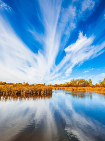cirrus: Cirrus clouds are reflected in the Winnipeg River. The concept of ecological and recreational tourism. Wonderful autumn day. Indian summer in Manitoba, Canada. Old Pinawa Dam Park