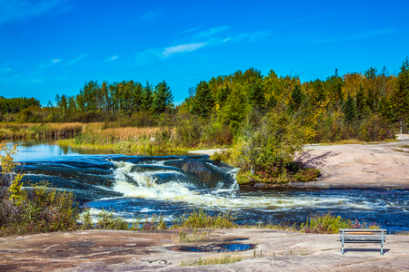 Foam water rapids on the smooth stones of the Winnipeg River. Warm autumn day. Trend of travel Around the World. Old Pinawa Dam Provincial Heritage Park Stock Photo