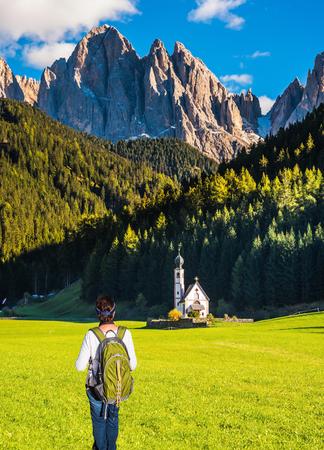 turismo ecologico: Soleado en Tirol. Activa anciana mujer-turista con mochila admirar la iglesia de Santa Maddalena. Montañas boscosas rodeadas de verdes prados alpinos. El concepto de turismo activo y ecológico