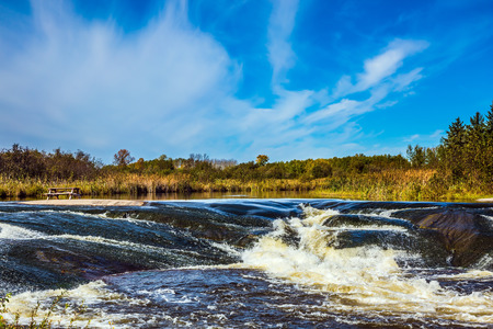 Old Pinawa Dam Park. Waterfall drain on the smooth stones of the Winnipeg River. The concept of ecological and extreme tourism