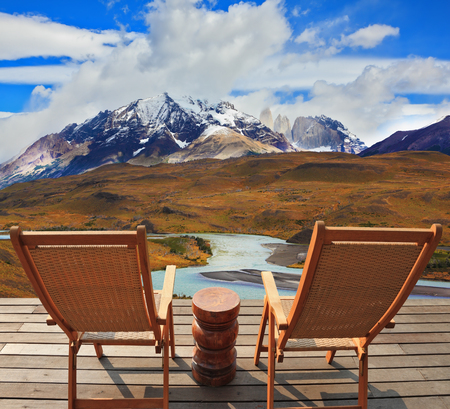 Pleasant holiday. Wooden chairs in the park Torres del Paine. Chile. On the horizon is visible snow-covered rocky mountain