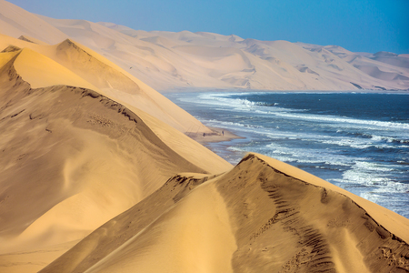 Atlantic coast of Walvis Bay, Namibia. Ocean surf with foamy waves.The concept of extreme and exotic tourism Stock Photo