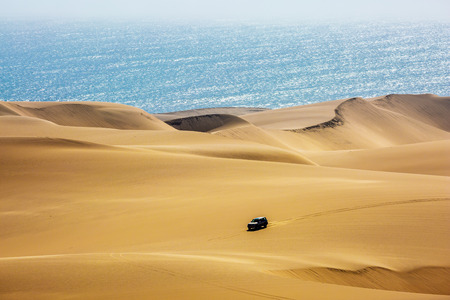 Atlantic coast of Namibia, south of Africa. Fantastic jeep - safari through the huge sand dunes on the ocean shore. The concept of exotic and extreme travel