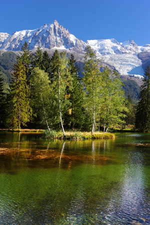 Snowy Alps picturesquely surrounded by evergreen trees and lake. Cozy urban park in Chamonix in sunset
