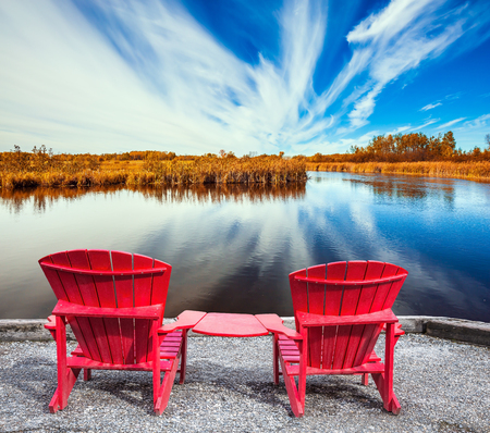 Cirrus clouds are reflected in the Winnipeg River. Lovely place to relax. Two red beach chairs on the riverbank. Old Pinawa Dam Park. The concept of ecological and recreational tourism Stock Photo
