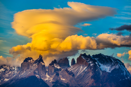 Magnificent cumulus clouds in the sunset. The black-and-steel color of the cliffs of Los Cuernos is covered with snow and ice. The concept of extreme tourism. Torres del Paine National Park
