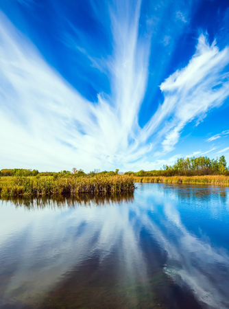 cirrus: Cirrus clouds are reflected in the Winnipeg River. The concept of ecological and recreational tourism. Indian summer in Canada. Old Pinawa Dam Park Stock Photo