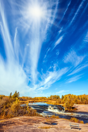 The concept of recreational and ecological tourism. Indian summer in Manitoba, Canada. Improbable plumose clouds and autumn sun over Winnipeg River