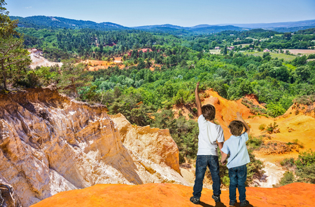 Two boys of seven and four years admired the magnificent nature. Orange and red picturesque hills. Languedoc - Roussillon, Provence, France Banco de Imagens