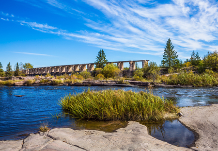 Indian summer in Manitoba, Canada. The ruins of old dam in Old Pinawa Dam Park. The concept of ecological and recreational tourism
