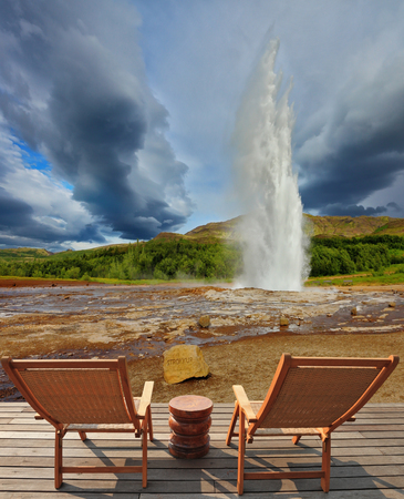 Pillar of hot water and steam from forcing its way out of the ground.  Geyser Strokkur in Iceland. Two lounge chairs and  small table on  wooden platform for easy observation