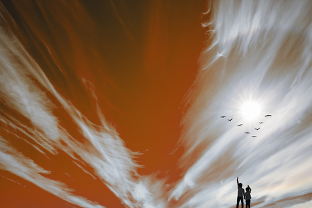Two boys look at the fire and birds. The sun makes its way through the flashes of red and white fire