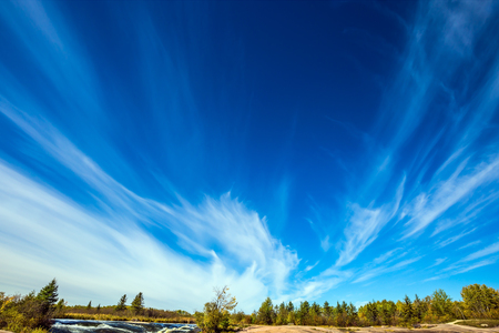 turismo ecologico: Cirrus clouds and strong wind.  Old Pinawa Dam Provincial Heritage Park, Canada. Warm autumn day.  The concept of ecological and recreational tourism