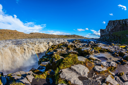 Colossal Dettifoss waterfall in Iceland. Sunset on a summer day,  magnificent rainbow in the water foam Stock Photo
