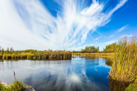 cirrus: Old Pinawa Dam Provincial Heritage Park. The concept of travel Around the World. Weak northern autumn sun and thin cirrus clouds is reflected in the Winnipeg River Stock Photo