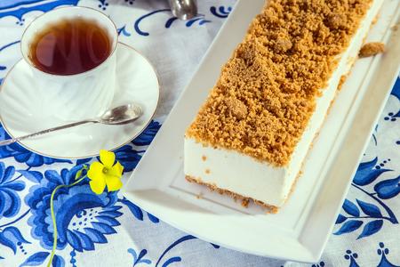 화려한 하얀 치즈 케이크, 달콤한 부스러기와 함께 뿌렸다. 전문 빵집. 배경은 뜨거운 차를 가진 도자기 컵이다.
