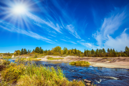 Indian summer in Manitoba, Canada. Improbable plumose clouds and the autumn sun over the river Winnipeg. The concept of ecological and recreational tourism Stock Photo