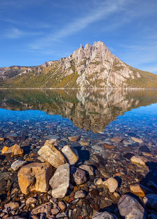 Picturesque mountain in the city of San Carlos de Bariloche, Argentina. The mirror water of shallow lake reflects sharp peaks and rocks. The concept of exotic and extreme tourism