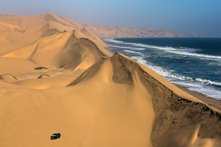 Magical jeep - safari through the sand dunes on the ocean shore. Atlantic coast of Namibia, south of Africa. The concept of exotic and extreme travel