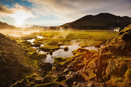 Above the source of thermal water steam rises. White nights in Iceland. Sunrise Park Landmannalaugar Stock Photo